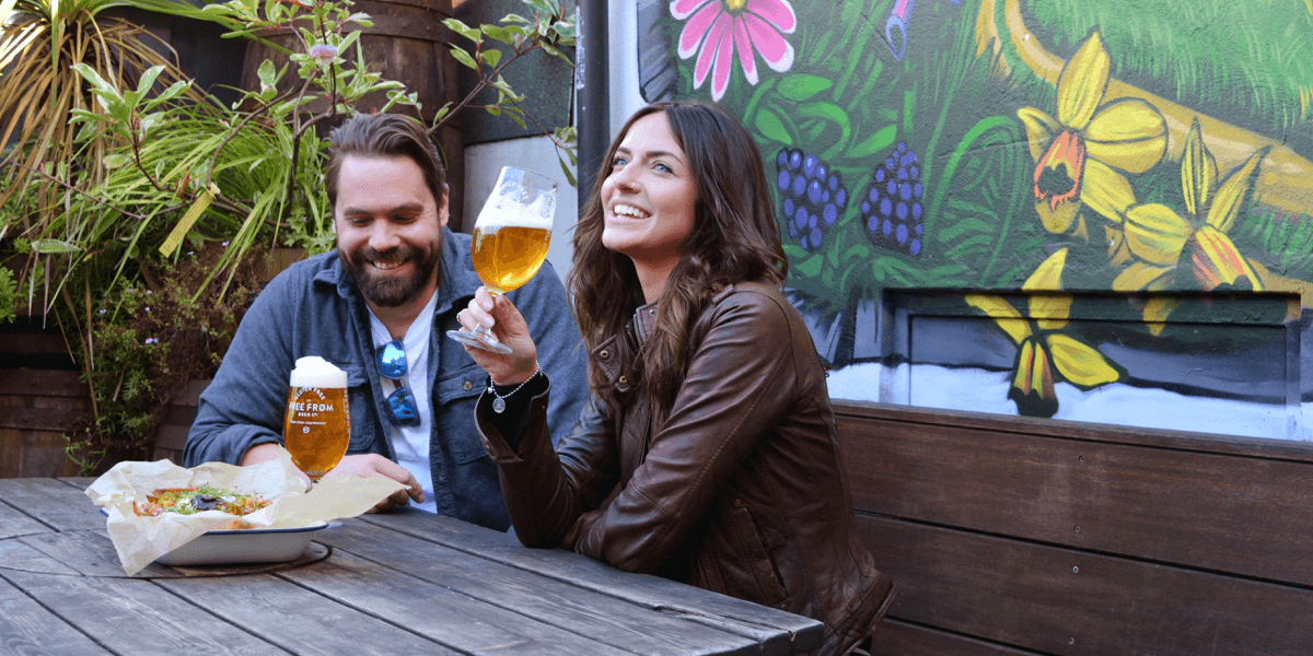 Man and women in pub garden drinking pint of free from beer