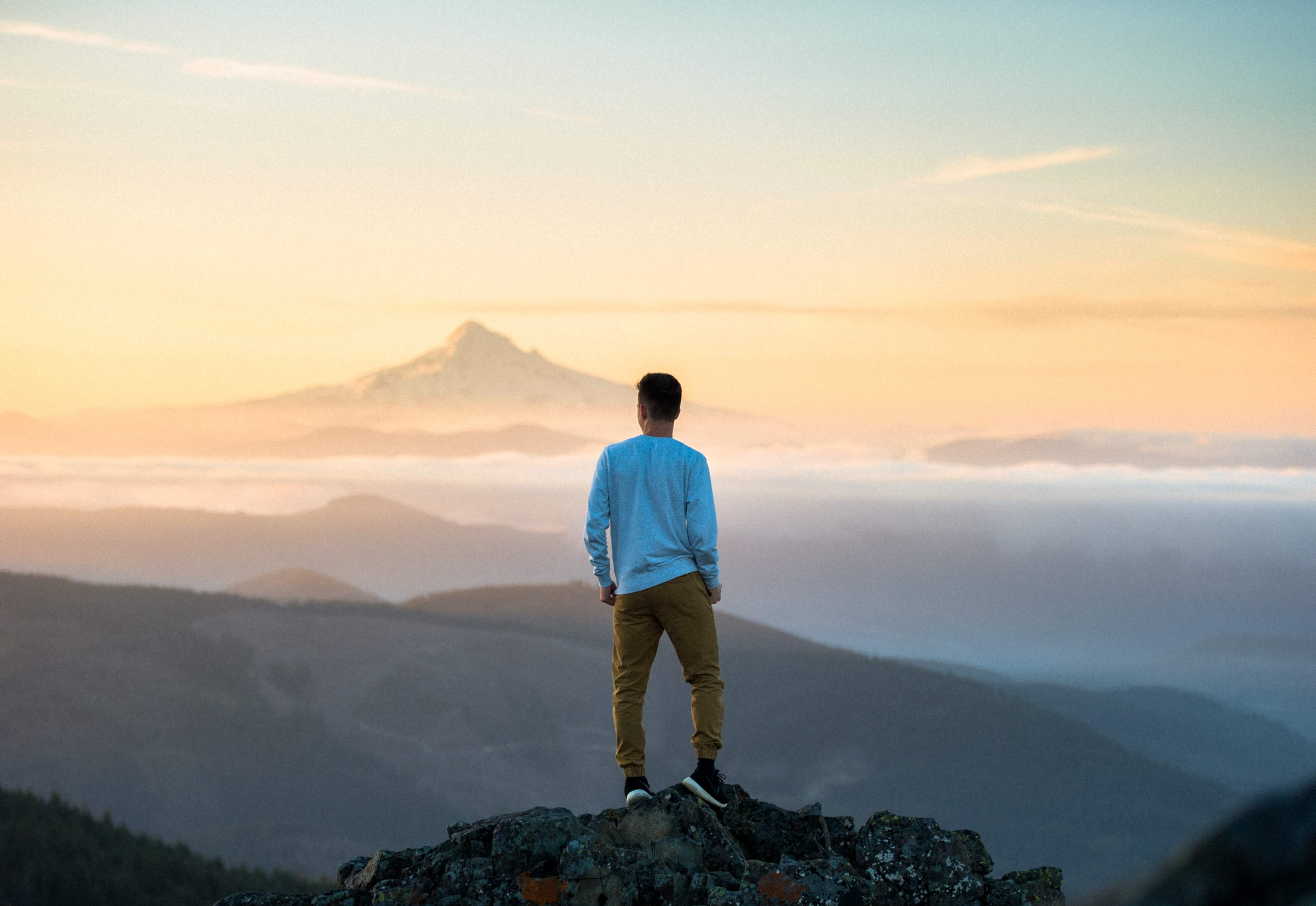 Searching for new horizons. Man on top of mountain